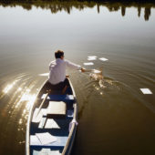 Man in a boat fishes paper out of the water.